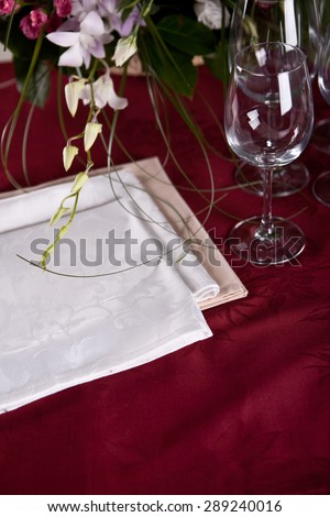 Luxury white serviettes on the red table-cloth with flowers