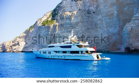 Luxury white yacht navigates into beautiful blue water near Zakynthos. View from the top of a large white yacht at Navagio Beach. - stock photo