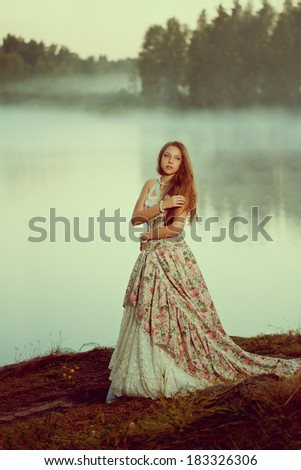 Luxury woman in a forest in a long vintage dress near the lake. Girl meets sunrise in summer forest