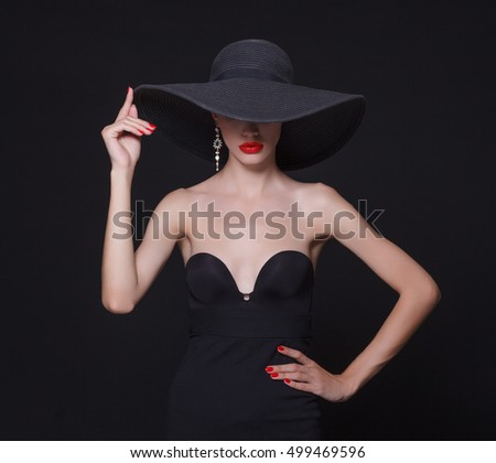 Luxury woman in a large black hat and bright lips on black background