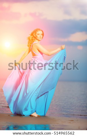 Luxury woman in a long blue evening  dress on the beach. Beautiful young girl at the 