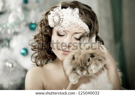 Luxury woman in fashion interior with bunny - stock photo