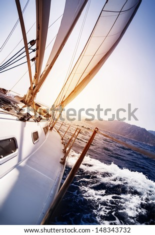 Luxury yacht in action in the sea on sunset background, sailing sport, water transport, summer cruise, traveling and tourism concept - stock photo