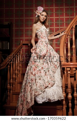 Luxury young smiling beautiful woman in vintage dress in elegant interior on the staircase