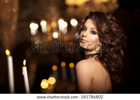 Luxury young woman in expensive interior. Girl with flawless makeup and evening volume hairstyle. - stock photo