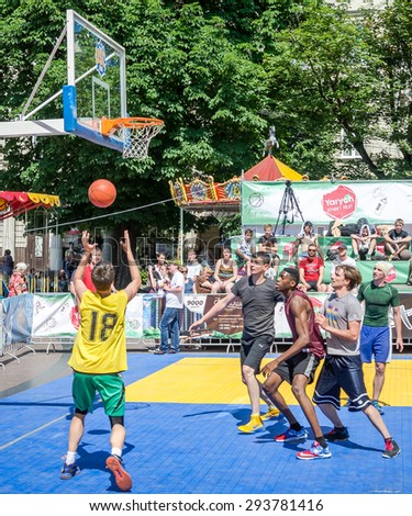 Lviv, Ukraine - July 2015: Yarych street Fest 2015. Street basketball competition at the festival near Lviv Opera House. Players fight for the ball under the basket - stock photo
