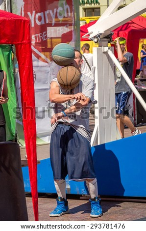 Lviv, Ukraine - July 2015: Yarych street Fest 2015. Street basketball competition at the festival near Lviv Opera House. Player juggles two balls - stock photo