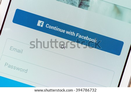 LVIV, UKRAINE - March 21, 2016: White Smart Phone with Log In Screen registration by Facebook Social Network  account