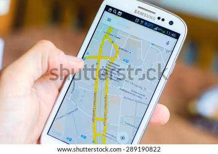LVIV, UKRAINE - May 19, 2015: Hand holding white Samsung Smart Phone with Google map application - stock photo