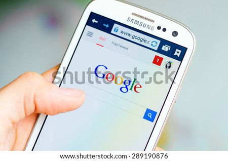 LVIV, UKRAINE - May 19, 2015: Hand holding white Samsung Smart Phone with Google search site - stock photo