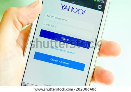 LVIV, UKRAINE - May 19, 2015: Hand holding white Samsung Smart Phone with Yahoo Log In Screen - stock photo