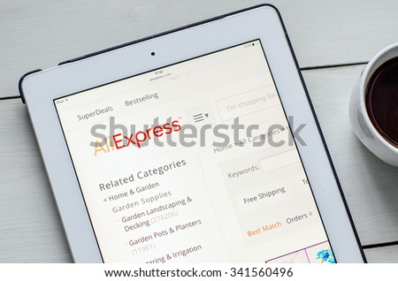 LVIV, UKRAINE - Sept 17, 2015: White ipad with AliExpress site application on screen, on white wood desk, and cup of coffee - stock photo