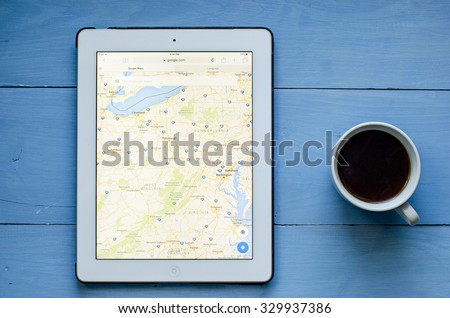 LVIV, UKRAINE - Sept 17, 2015: White ipad with Google map application on screen, on blue  wood desk - stock photo