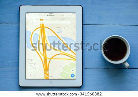 LVIV, UKRAINE - Sept 17, 2015: White ipad with Google map application on screen, on blue  wood desk - stock photo