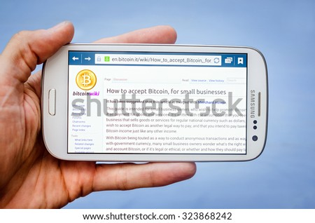 LVIV, UKRAINE - Sept 30, 2015: white Samsung Smart Phone with wikipedia page  about bitcoin for business ,  in hand - stock photo