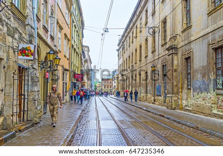 LVOV, UKRAINE - MAY 16, 2017: The old town Ruska street during the rain - people hides under umbrellas, the floor becomes wet and shiny, on May 16 in Lvov.
