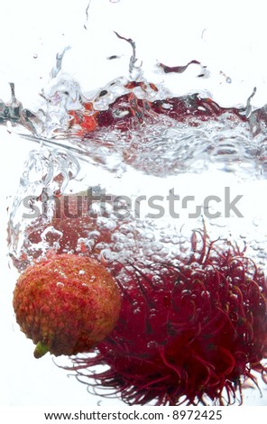 Lychee and Rambutan thrown in water - stock photo