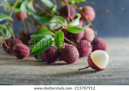 Lychee with leaves on a wooden table - stock photo