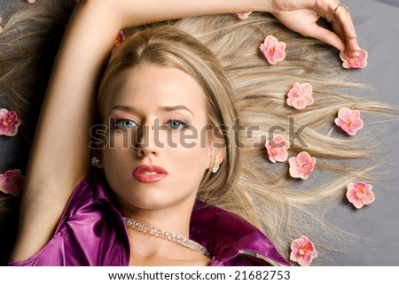 lying beautiful woman with pink flowers