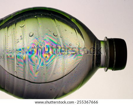 Lying bottle of fizzy drink, with refraction effect, rainbow. Unusual.