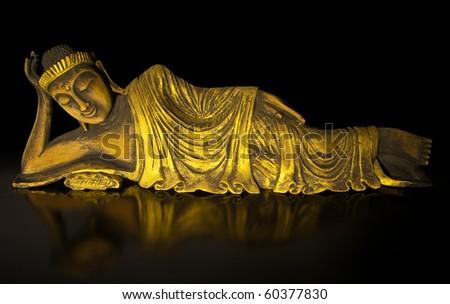 Lying Buddha statue made of teak wood on black. - stock photo
