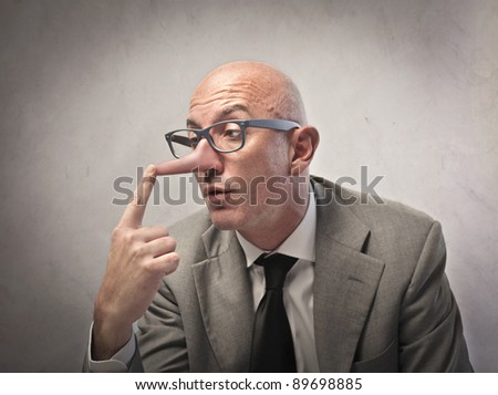 Lying businessman observing his long nose - stock photo