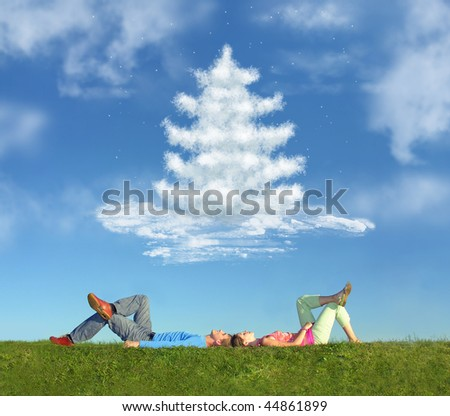 lying couple on grass and dream christmas tree collage - stock photo