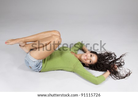 Lying model posing in the studio with gray background - stock photo