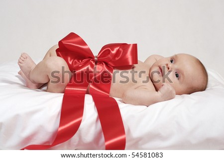 lying newborn baby on the pillow wrapped up with red big bow - stock photo