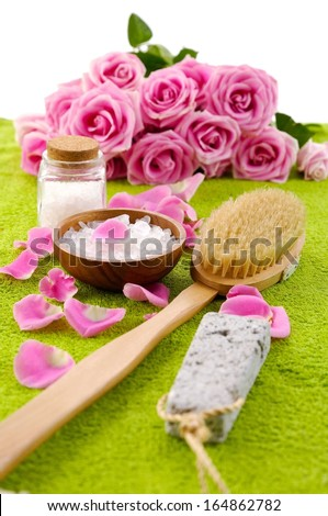 lying on branch roses with petals and salt in bowl with brush on green towel  - stock photo