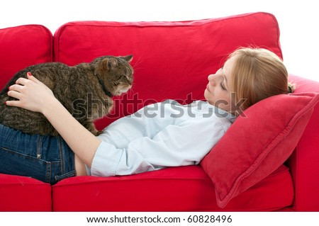 lying on red sofa young woman with  cat - stock photo