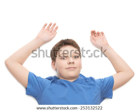 Lying on the white surface young boy in a blue t-shirt with a weird facial expression, portrait isolated over the white background - stock photo