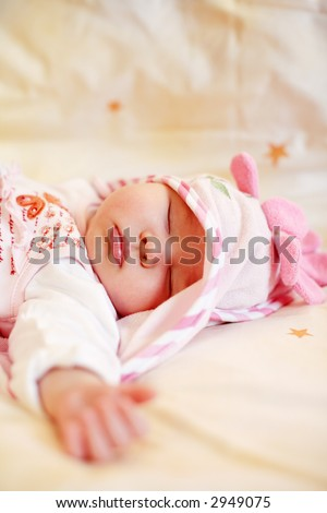 Lying sleeping baby with small teddy bear on bright background