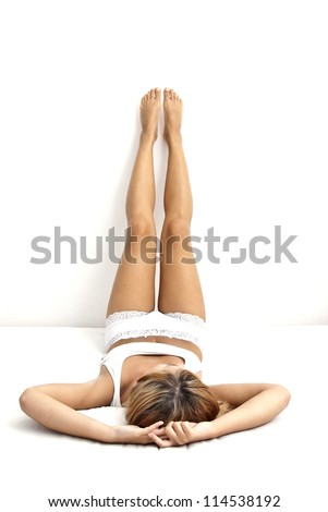 Lying woman in lingerie, natural body and legs - stock photo
