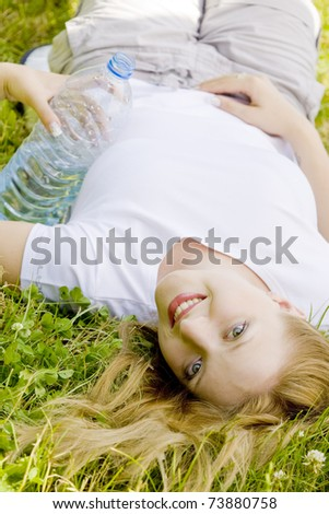 lying woman with bottle of water - stock photo