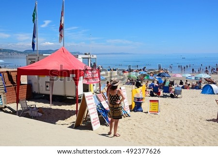 LYME REGIS, UNITED KINGDOM - JULY 18, 2016 - Tourists relaxing on the beach with a deckchair and parasol rental tent in the foreground and the sea to the rear, Lyme Regis, England, UK, July 18, 2016.