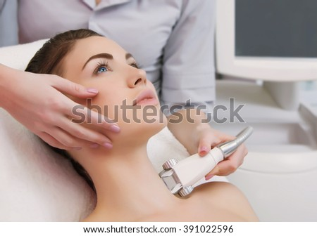 Lymphatic drainage massage LPG apparatus process. Therapist beautician makes a rejuvenating facial massage for the model  in a beauty salon. Close up, selective focus. - stock photo