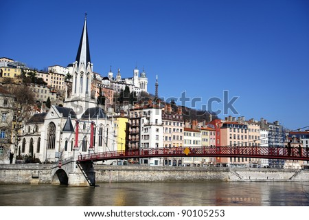 Lyon city with church and red footbridge in blue sky - stock photo