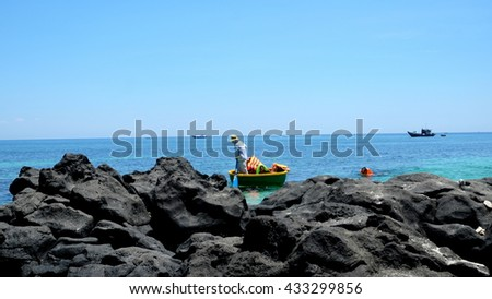 LYSON ISLAND, QUANG NGAI PROVINCE, VIETNAM - JUNE 2016: Unidentified fisherman is dragging the punt on the blue sea of Ly Son island. Ly Son is an ancient volcanic island.