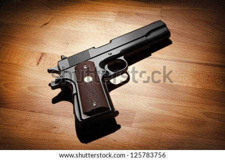 M1911 semi-automatic .45 caliber pistol on a wooden surface. Studio shot - stock photo