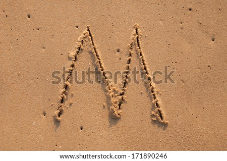 M text written in the sandy on the beach - stock photo