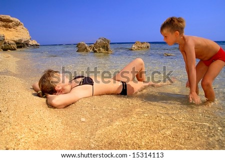 ma and son playing on beach on background blue sky