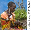MAASAI MARA, KENYA-DECEMBER 27: Maasai woman makes traditional necklace 27 December, 2012 at Maasai Mara, Kenya. The Maasai are the most famous tribe in Africa. - stock photo