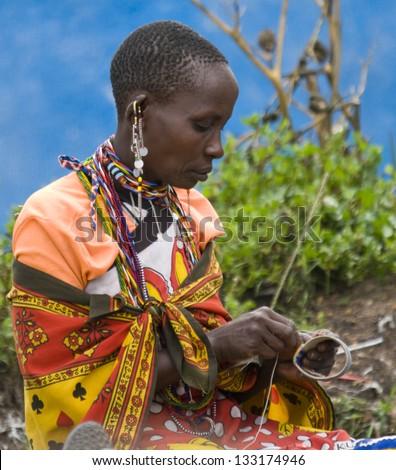 MAASAI MARA, KENYA-DECEMBER 27: Maasai woman makes traditional necklace 27 December, 2012 at Maasai Mara, Kenya. The Maasai are the most famous tribe in Africa. - stock photo