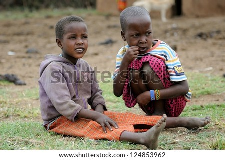MAASAI MARA, KENYA - NOVEMBER 10: Portrait of unidentified Maasai children on November 10, 2012 in Maasai Mara, Kenya. Maasai are a Nilotic ethnic group of semi-nomadic people located in Kenya - stock photo