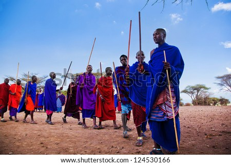 Maasai village, TANZANIA, AFRICA - DECEMBER 11: A group of Maasai men performing their ritual dance in traditional clothes in their village on December 11, 2012 in Tanzania. - stock photo