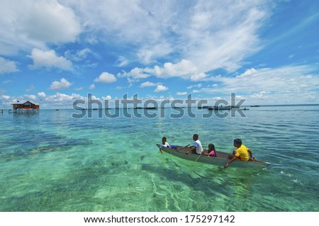 MABUL ISLAND,MALAYSIA - SEPTEMBER 20th 2012 : Unidentified Sea Bajau children on the raft in  Mabul Island Sabah,Malaysia.The Sea Bajau children here do not attend school due to lack of resources.