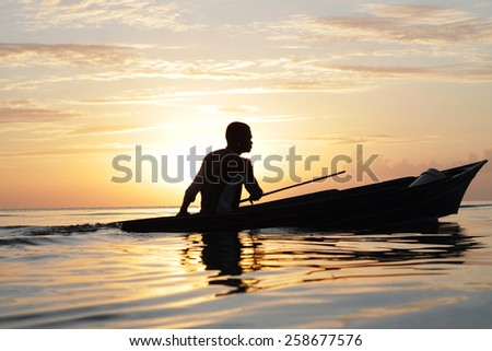 MABUL ISLAND, SABAH. 28 FEBRUARY 2015. Silhouette of sea gypsy boating across a sunset background at 28 FEBRUARY. The Sea Gypsies are sea nomads that move from one place to another.