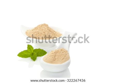 Maca powder on spoon and in a bowl and mint leaf isolated on white background. Natural alternative medicine. - stock photo