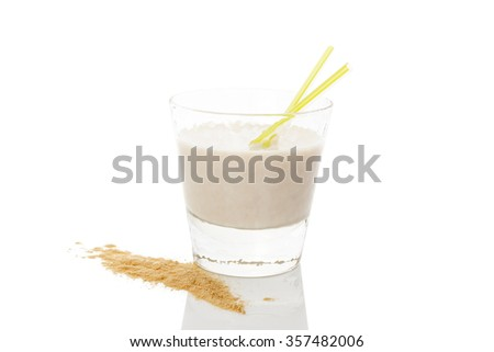 Maca powder on spoon and maca milkshake in glass isolated on white background. Natural alternative medicine.